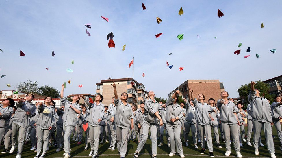 This photo taken on May 24, 2016 shows senior high students flying paper planes to release stress before the college entrance exams at a high school in Handan, north China's Hebei province