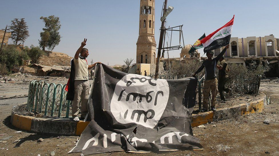 Fighters from the Hashed al-Shaabi (Popular Mobilisation units), backing the Iraqi forces, pose with a flag of the Islamic State (IS) group in Tal Afar on 27 August 2017