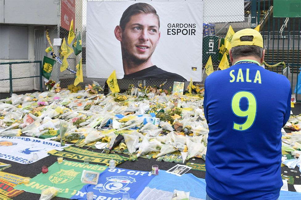 A supporter stands in front of flowers placed in front of a giant portrait of Emilianio Sala outside La Beaujoire stadium before Tuesday's French Cup match between FC Nantes and Toulouse FC
