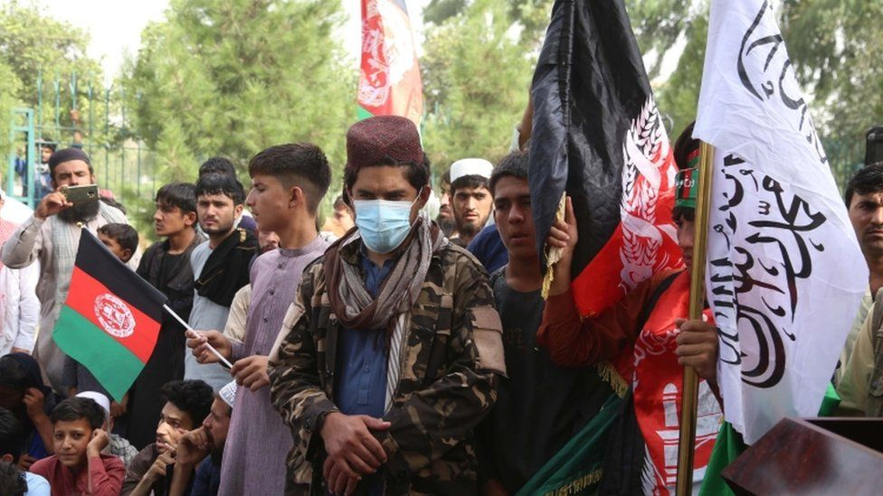 A Taliban stands guard as Afghans hold national flag as they celebrate the 102nd Independence day in Jalalabad, Afghanistan, 19 August 2021. Afghanistan is celebrating the 102nd anniversary of its independence from British rule on 18 August.