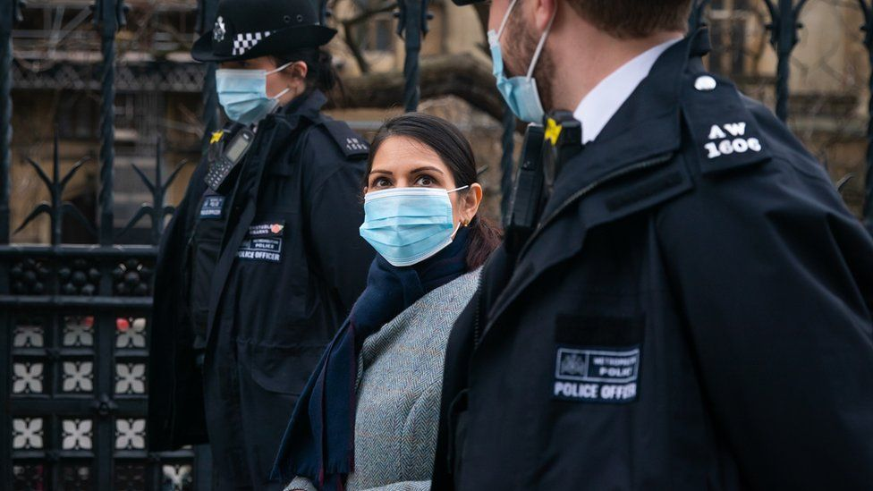 Priti Patel walks with two police officers