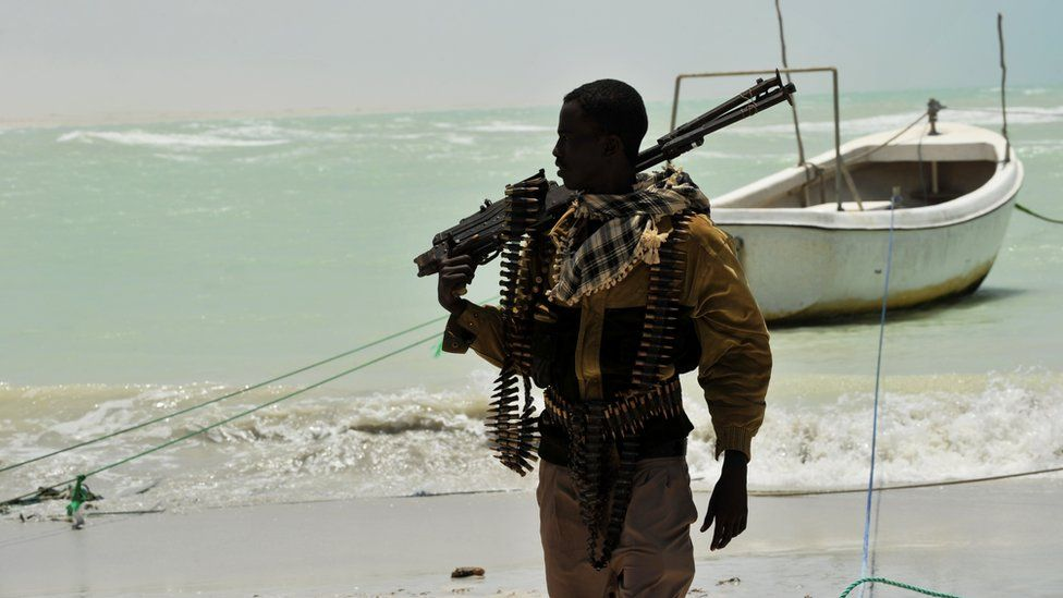 A Somali pirate carries a weapon on a beach in the central Somali town of Hobyo, 20 August 2010
