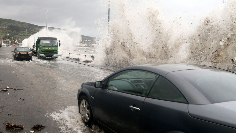Waves break over the shore and on to passing cars as they are driven along the coast road in Carnlough, Northern Ireland.