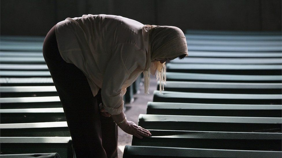 Relative of some of the Srebrenica massacre victims touches one of the 610 coffins containing the remains of family members at the Srebrenica Memorial site on 9 July 2005