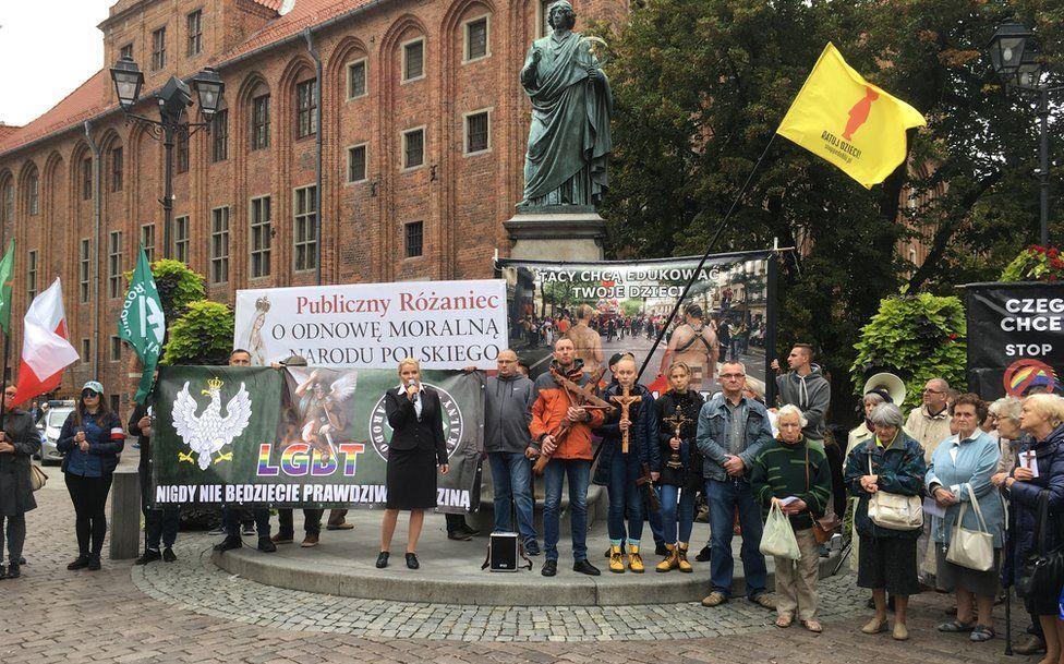 A small counter march in Torun assembled beneath a statue of Copernicus