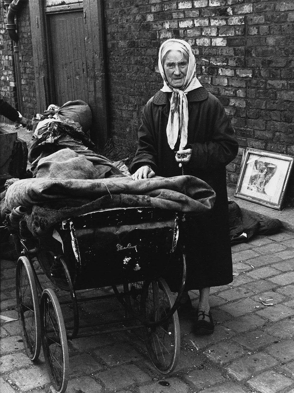 An elderly woman stands next to a pram with bundles of cloth on