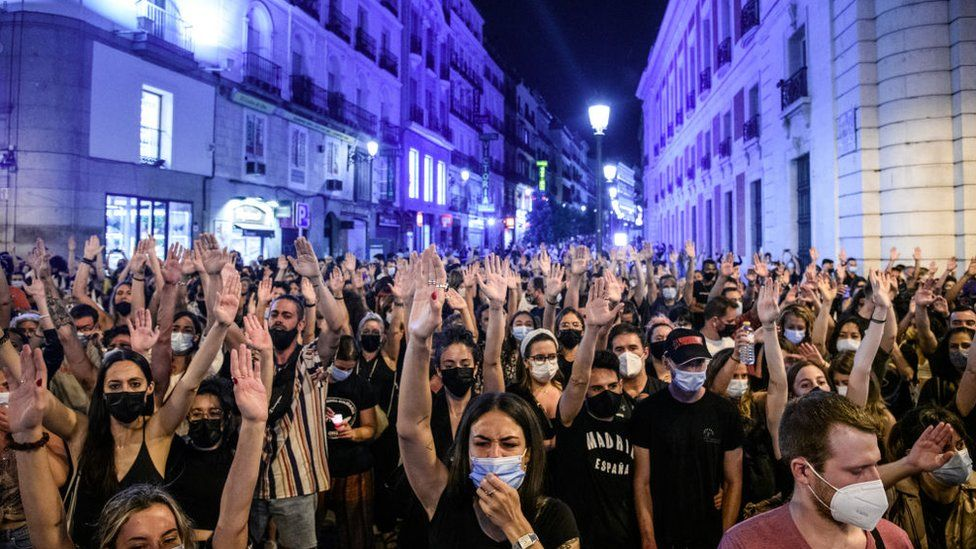 Protesters with their hands in the air