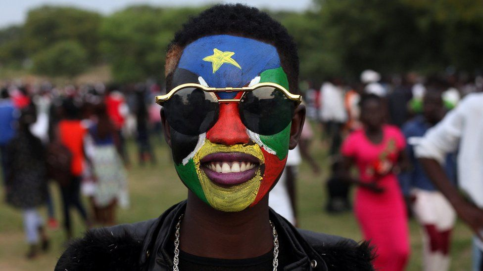 A woman with her face pointed in the colours of South Sudan's flag - Juba, July 2018