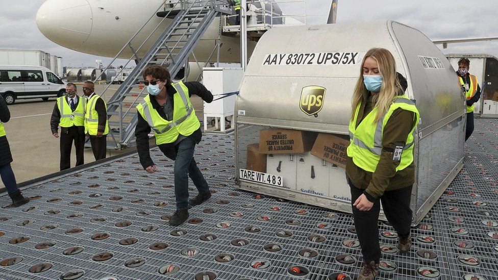 UPS employees move one of two shipping containers containing the first shipments of the Pfizer and BioNTech COVID-19 vaccine a ramp at UPS Worldport in Louisville, Kentucky, on December 13, 2020.