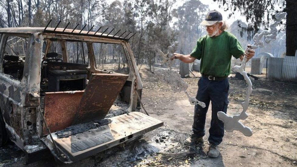 A man holding parts of melted metals surveys the destruction on his property in Torrington, NSW