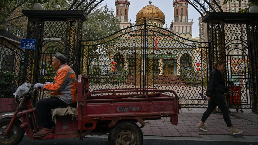 This photo taken on September 11, 2019 shows people walking past a mosque in Urumqi, the regional capital of Xinjiang.