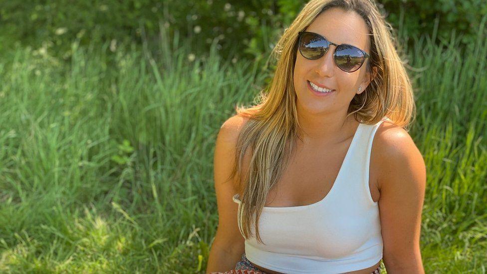 Аннабель сидит на траве в солнечных очках
