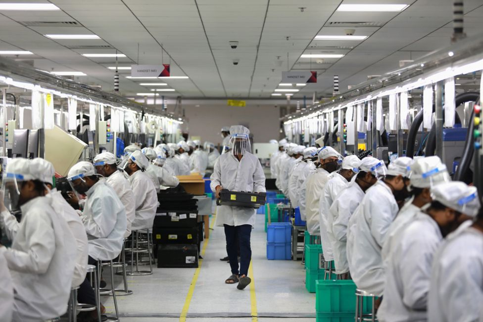 Workers wearing face shields work at an assembly line