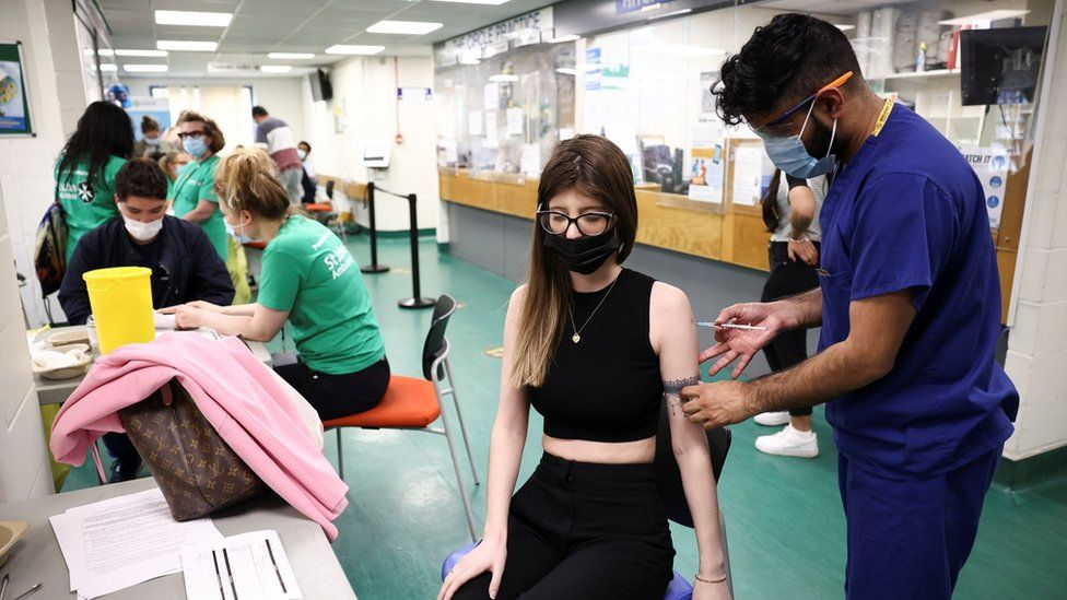 A person receives a dose of the Pfizer-BioNTech vaccine at a vaccination centre for those aged over 18 years old at the Belmont Health Centre in Harrow