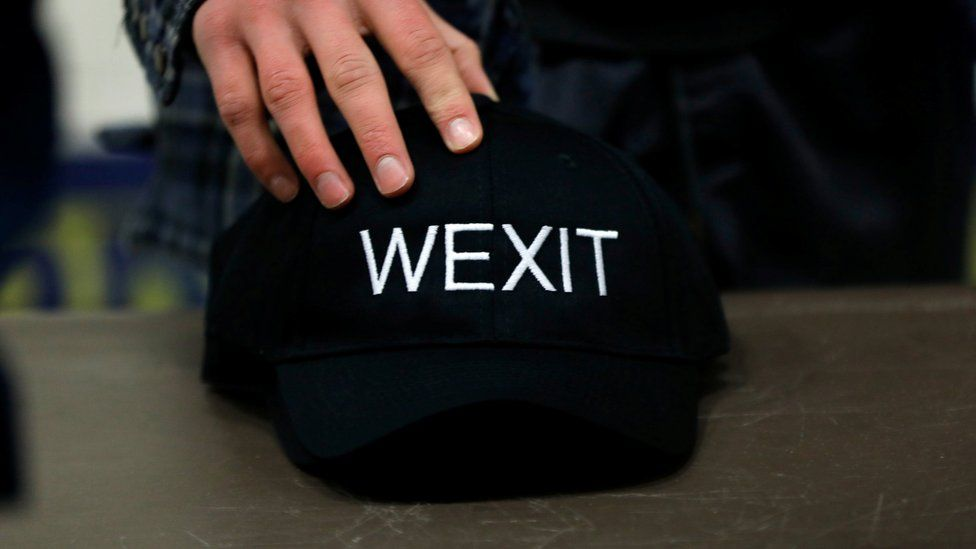 A supporter holds his Wexit hat while attending a rally for a separatist group seeking federal party status