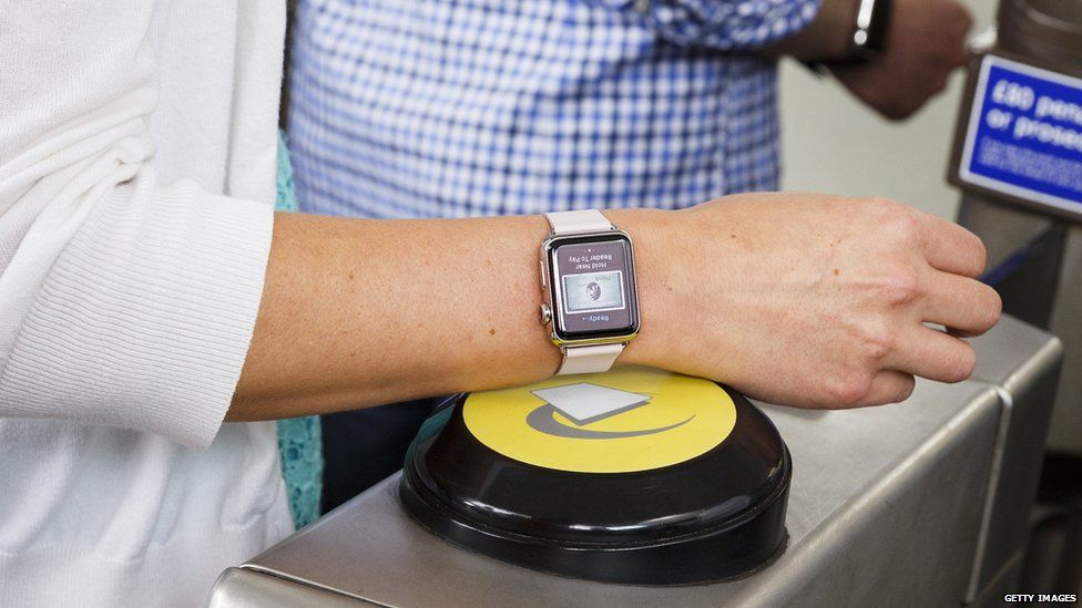 Someone touching an Apple Watch on to a contactless reader