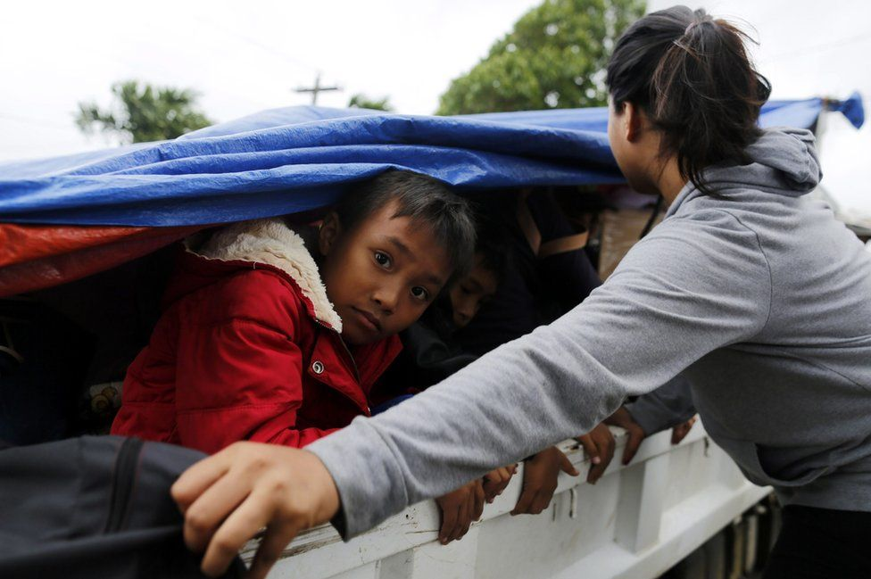 Filipino children shelter under a tarpaulin on a truck during evacuation in the town of Aparri, Cagayan province, Philippines, 19 October 2016