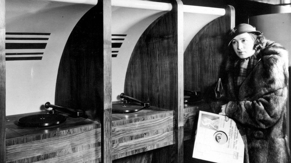 A woman at the first listening booths in HMV in the 1930s