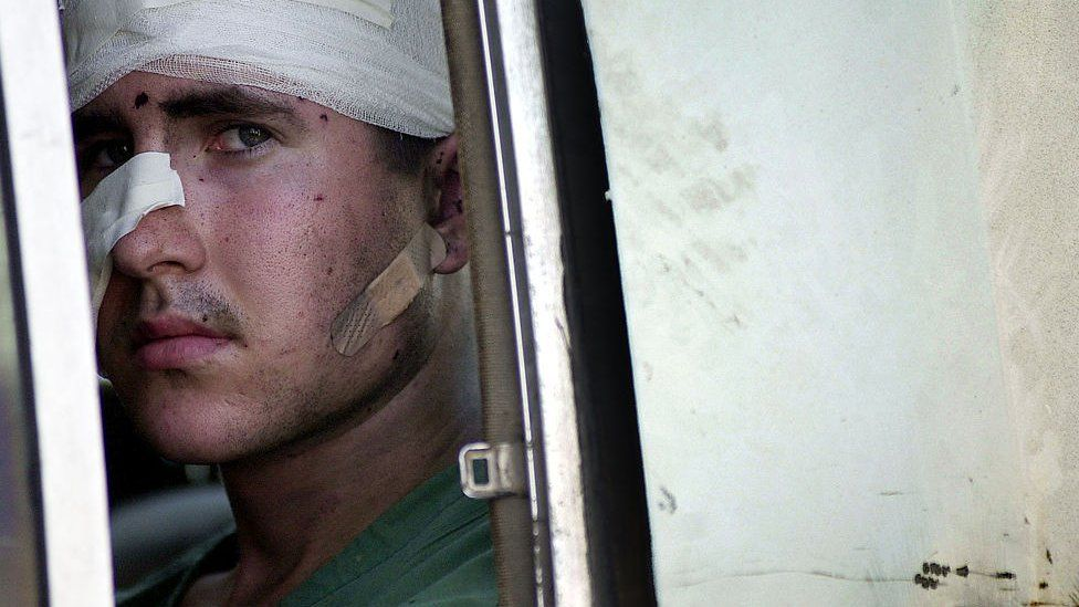 A wounded American sailor from the USS Cole being taken to a Yemeni hospital, 12 October 2000