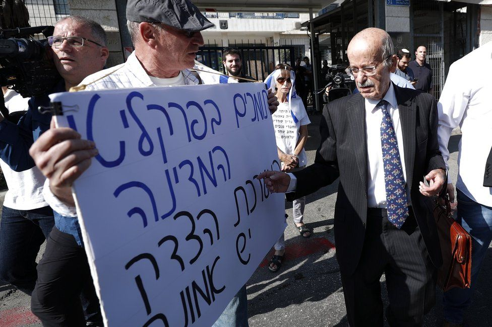 """Benjamin Netanyahu's lawyer, Ram Caspi (right), walks past a man carrying a poster saying """"We support the state prosecutors and the justice system"""", as he arrives at the Israeli justice ministry in Jerusalem (2 October 2019)"""