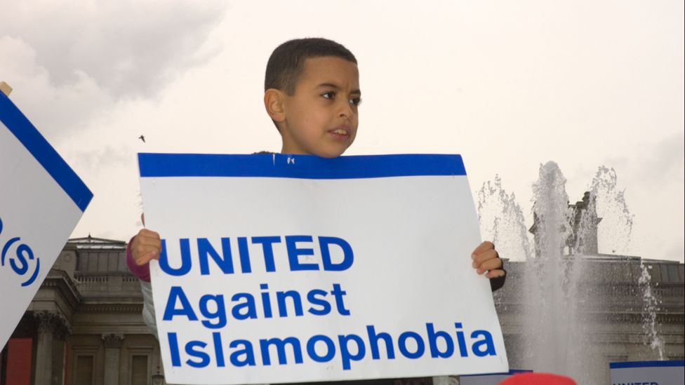 """A boy holds up a placard reading """"United against Islamophobia"""""""