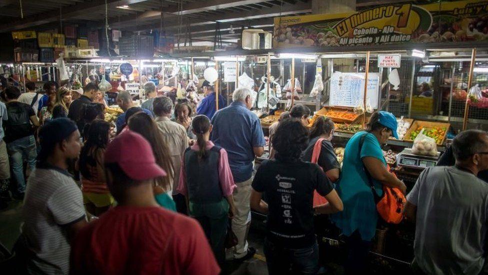 Venezuelans shop in a municipal market in Caracas on 18 August 2018.
