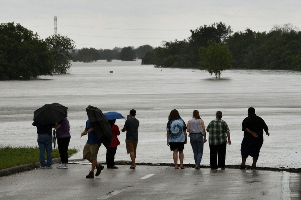 Local residents check the water level of the Barker Reservoir after the Army Corp of Engineers started to release water into the Clodine district as Hurricane Harvey caused heavy flooding in Houston, Texas on 29 August 2017.