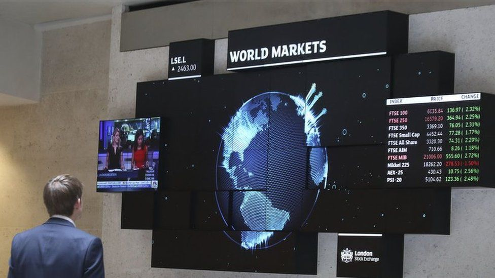 A city worker looking at a stock ticker screen at the London Stock Exchange in the City of London, August 2015