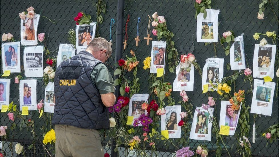 A man prays in front of a missing persons wall near a collapsed apartment block in Miami, Florida, June 2021