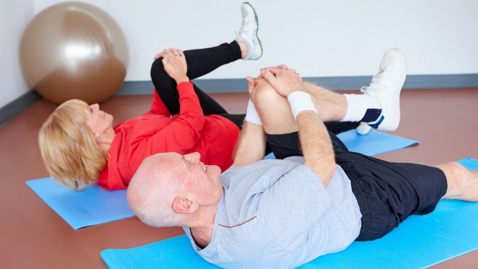 Man and woman exercising on a gym mat