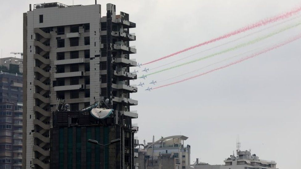 Aircraft fly past damaged buildings and release smoke in the colours of the Lebanese flag as French President Emmanuel Macron visits Lebanon, (1 September 2020)