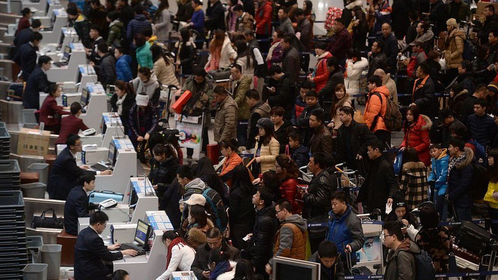 Passengers checking in at the service counters in Beijing Capital International Airport on the first day of China's spring festival travel rush in Beijing