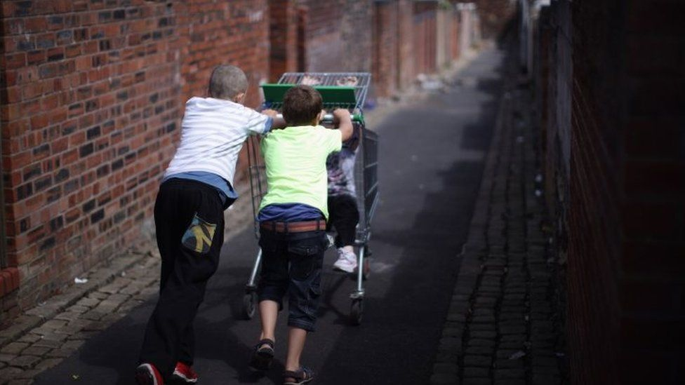 Children play with a discarded shopping trolley in the back alleys