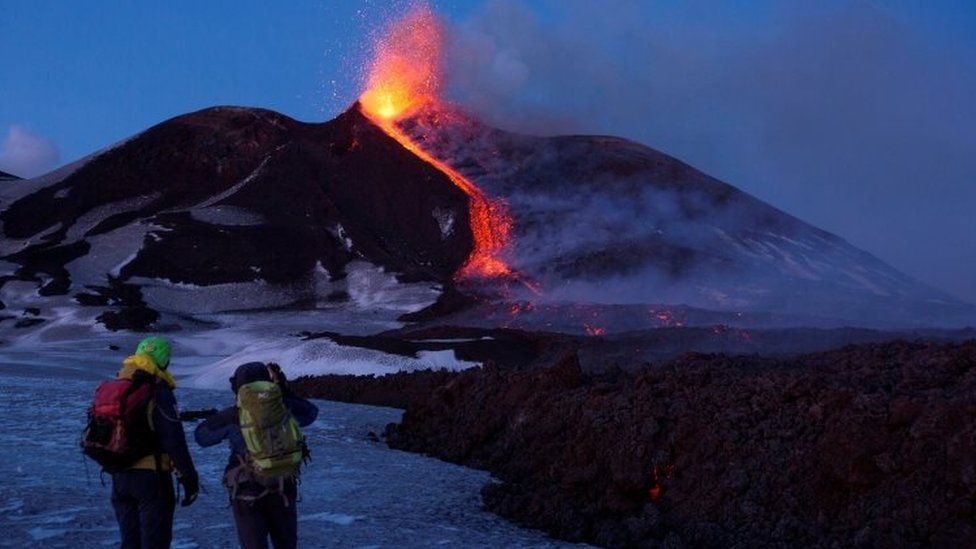 """Volcano guides stand in front of Italy""""s Mount Etna, Europe""""s tallest and most active volcano"""