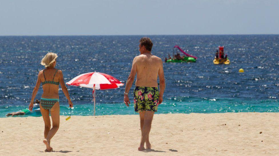 Tourists walk at Magaluf Beach in Calvia, on the Balearic Island of Mallorca.