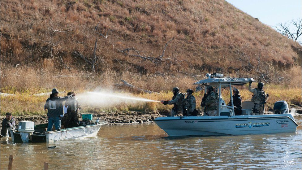 Police use pepper spray against protesters in a boat during a protest against the building of a pipeline on the Standing Rock Indian Reservation near Cannonball, North Dakota