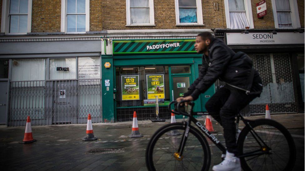 A young man rides a bicycle past a betting shop