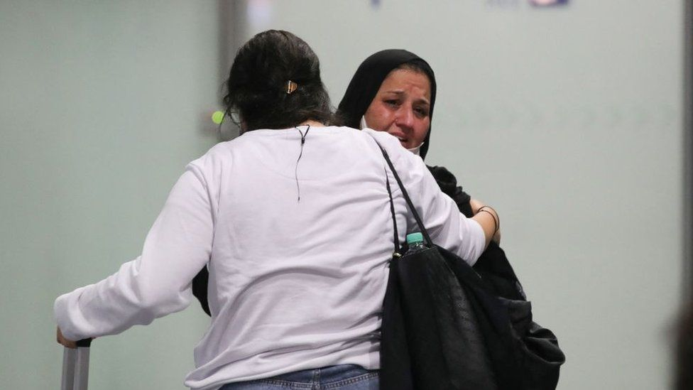A woman weeps as she arrives among the first German and Afghan evacuees from Kabul, at Frankfurt International Airport