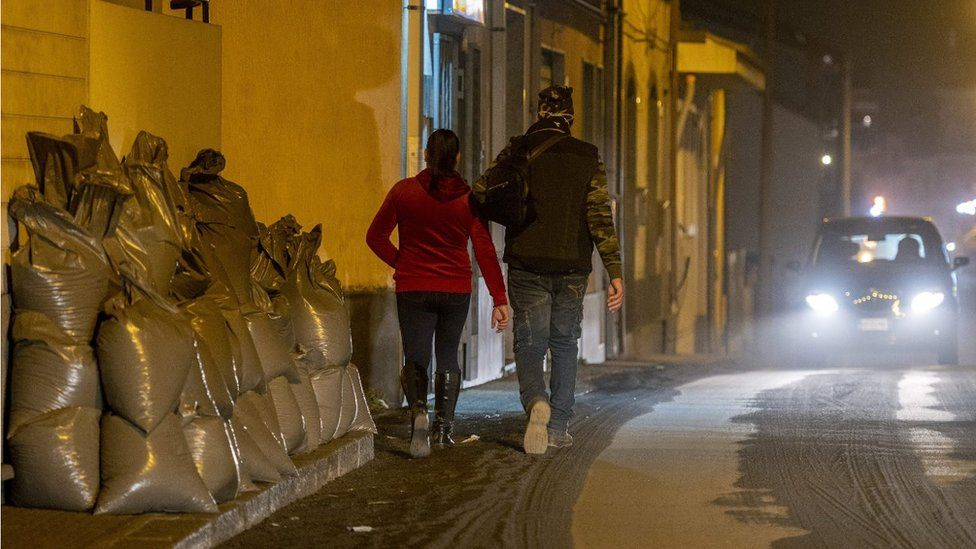 Residents walk on ashes, past bags filled with ashes from the Mount Etna volcano stored aside after being swept by municipal employees from a street of Zafferana Etnea, north of Catania,