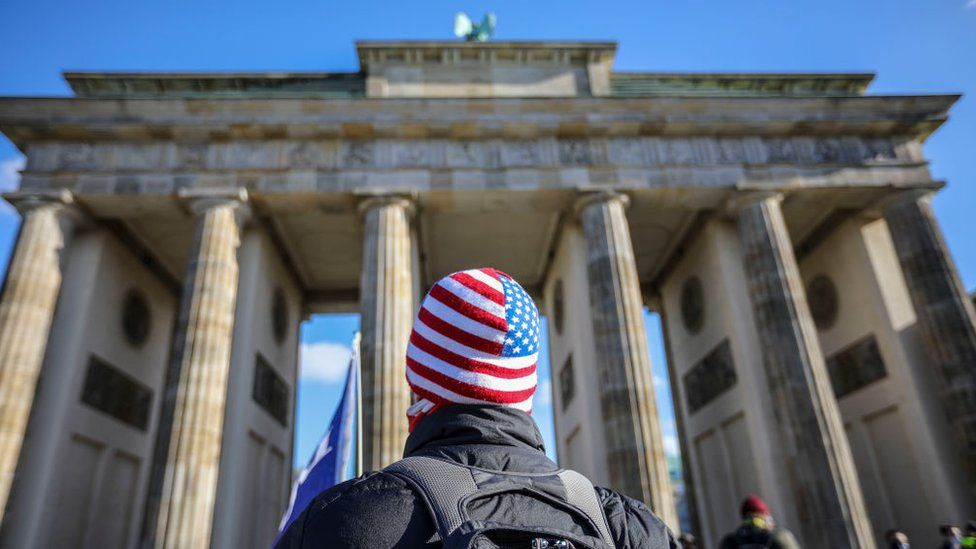 A man in a US flag hat stands in front of Brandenburg Gate
