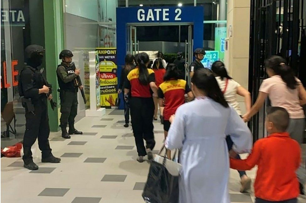 Security forces evacuate people from the shopping complex