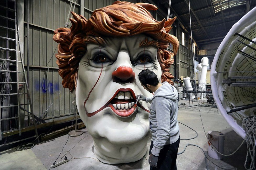 A man paints a giant model of a head