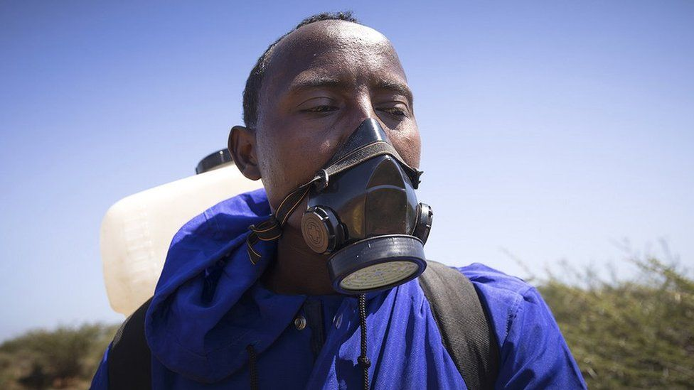 Man with face mask and spray canister in Ethiopia