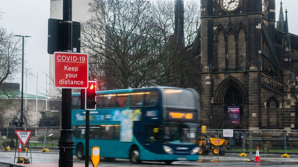 Newcastle civic centre with a bus in front of it and Covid sign