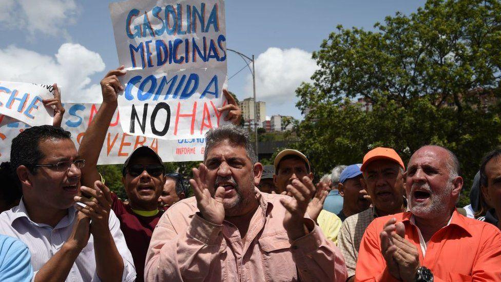 """Manifestantes protestan contra el gobierno de Nicolás Maduro con un cartel que dice """"Gasolina, medicinas, comida, no hay""""."""