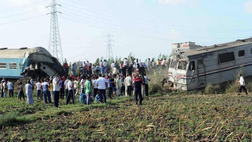 People gather at the site of a train collision in the area of Khorshid, in Egypts Mediterranean city of Alexandria
