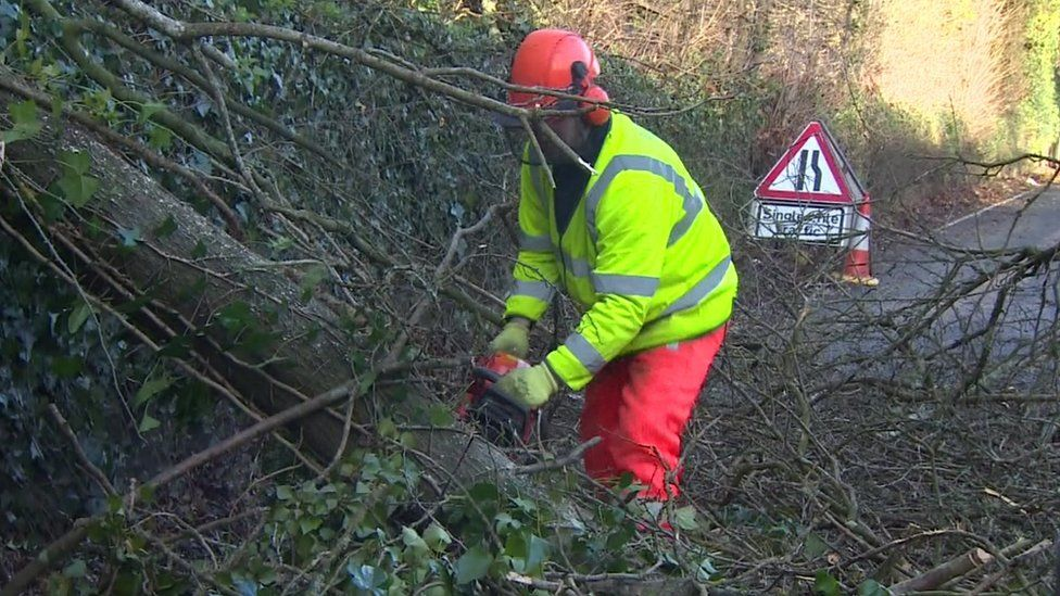 Highway Agency worker cutting debris out the road