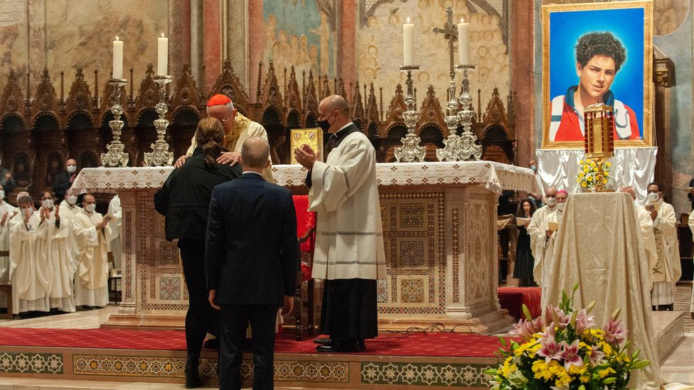 Cardinal Agostino Vallini greets the mother and father of Carlo Acutis as he celebrates Mass for the beatification process