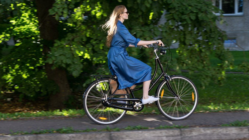 Woman cycling on path