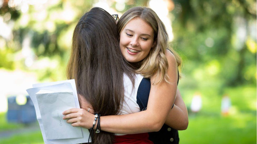 Chloe Orrin hugs a friend after opening her GCSE results at Ffynone House school on August 20, 2020 in Swansea, Wales